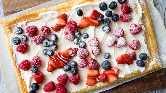 An overview of a full puff pastry tart with whipped greek yogurt and berries on top.