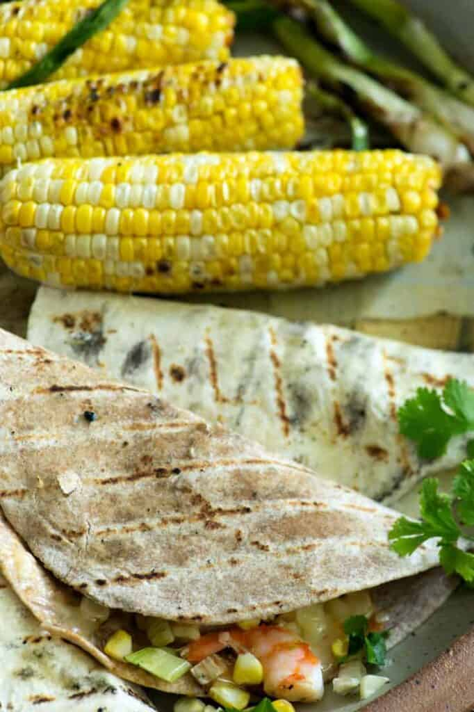 What To Serve With Corn On The Cob. Corn tortillas with veggies and shrimp grilled on a platter with corn on the cob sitting alongside it.