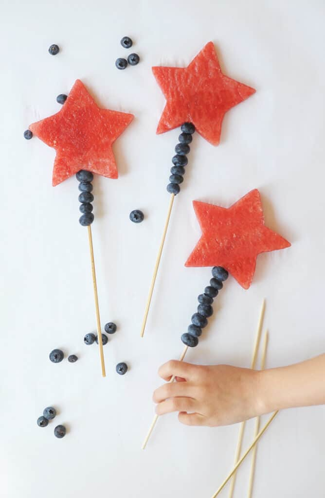 A hand picking up 4th of July watermelon wands with whole blueberries around the fruit wands.