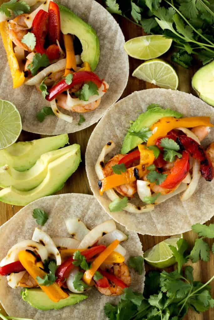 Cilantro and lime wedges alongside open faced corn tortillas stuffed with grilled shrimp, peppers and onions.