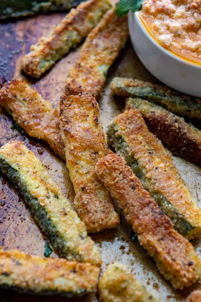 zucchini fries on a baking sheet with a dipping sauce in a bowl alongside.