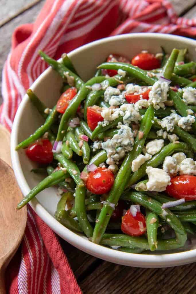 Bowl of marinated green bean salad on a table.