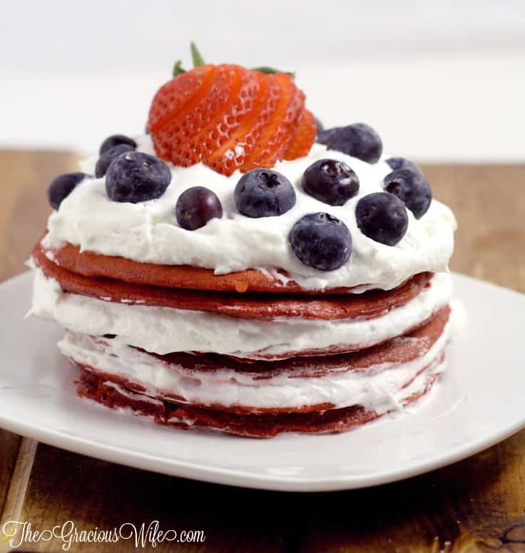 A stack of red velvet pancakes with strawberries and blueberries on top with whipped cream between each layer.