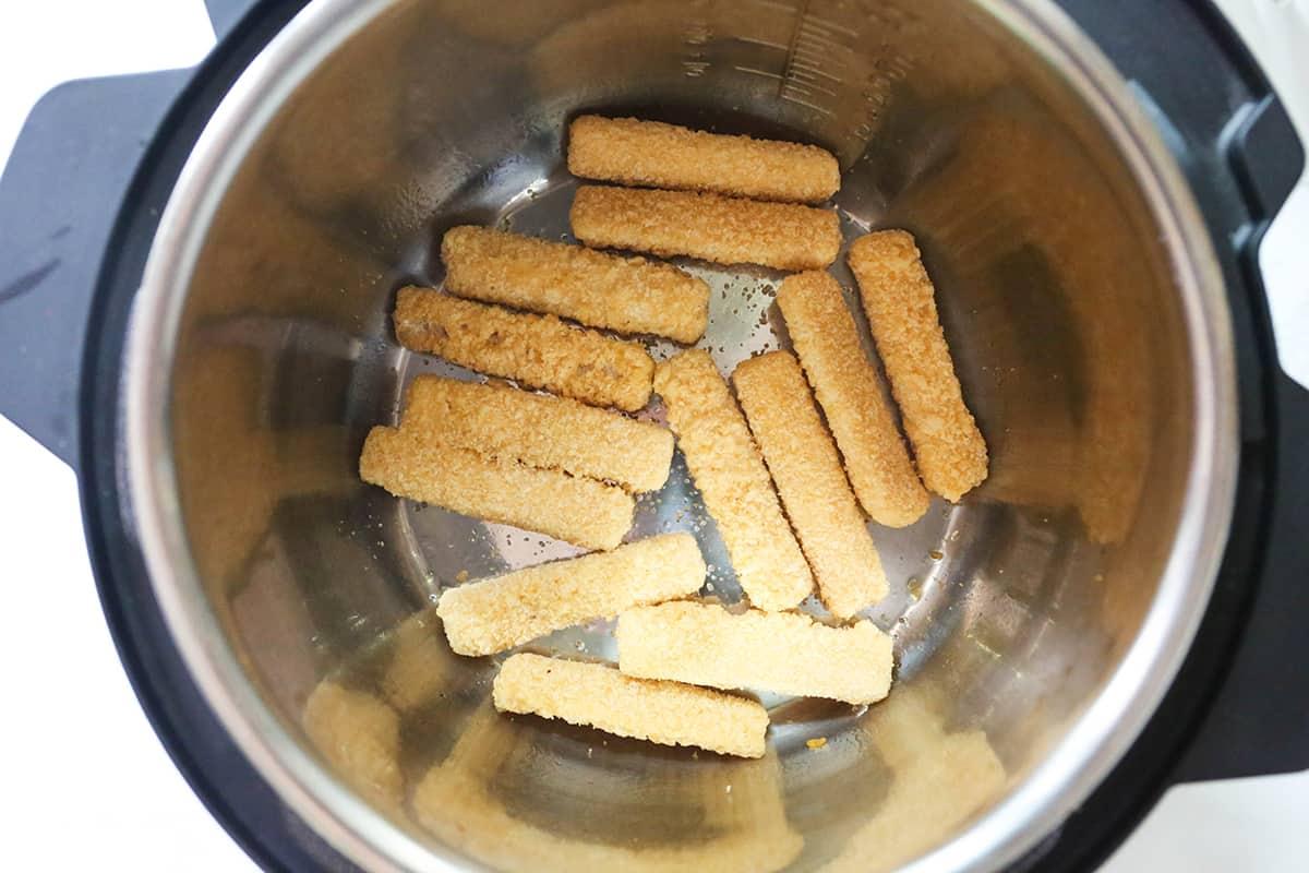 Frozen fish sticks in a single layer inside an air fryer.