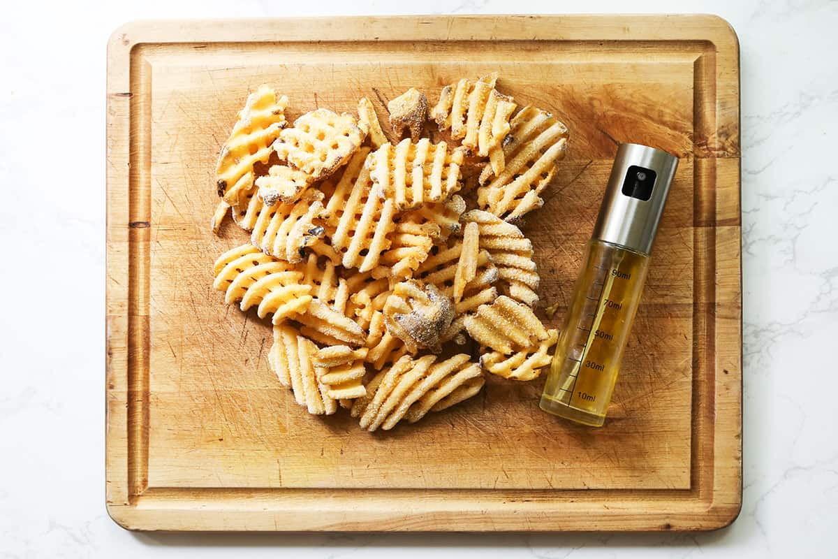 Frozen waffle fries on a cutting board next to olive oil spritzer.