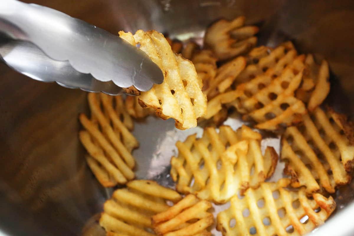 Tongs flipping waffle fries inside an air fryer.