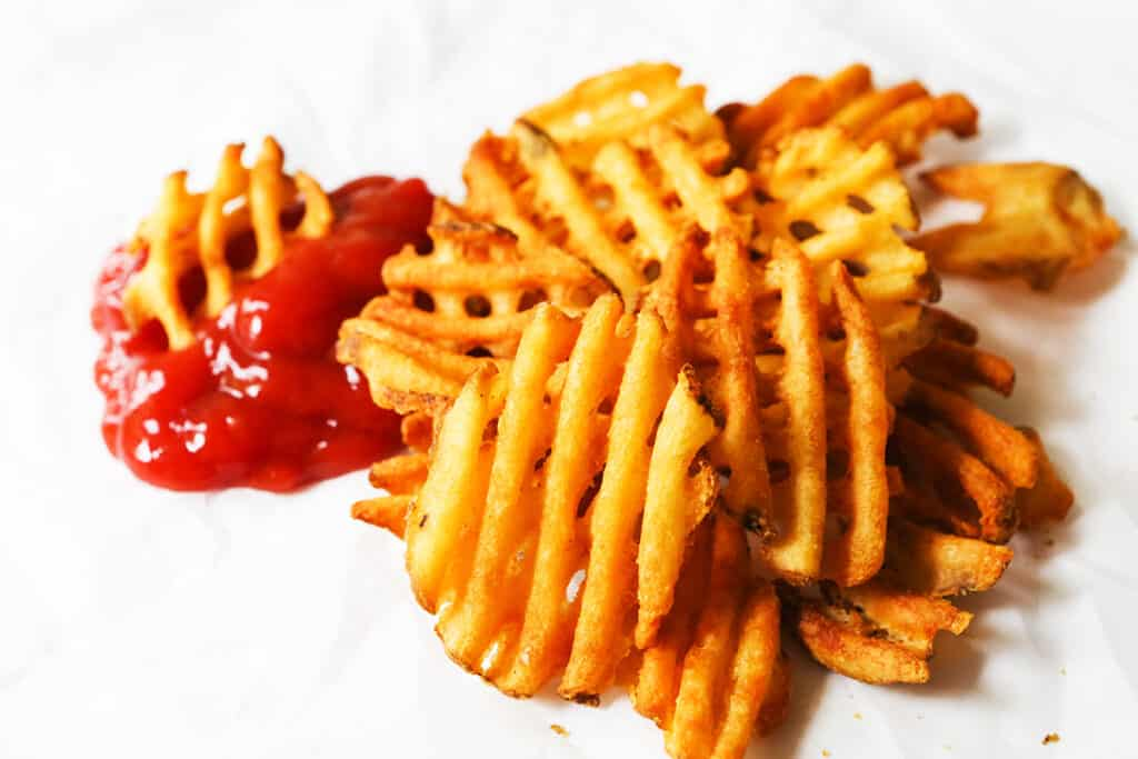 A pile of waffle fries next to some ketchup.