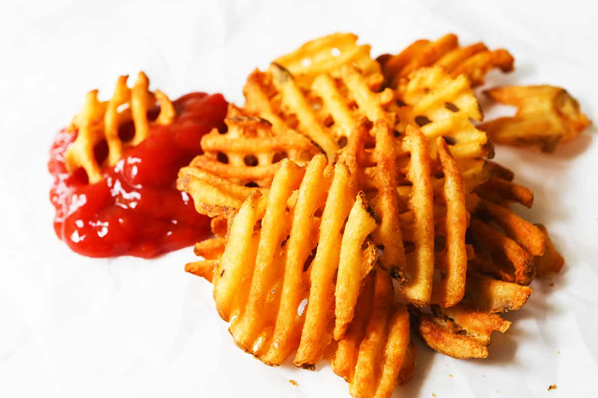 Pile of waffle fries next to ketchup.