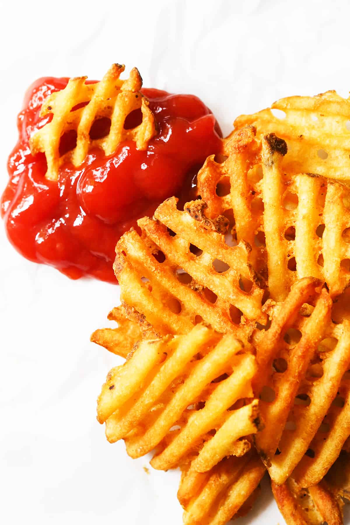 Waffle fries stacked on parchment next to a glob of ketchup.