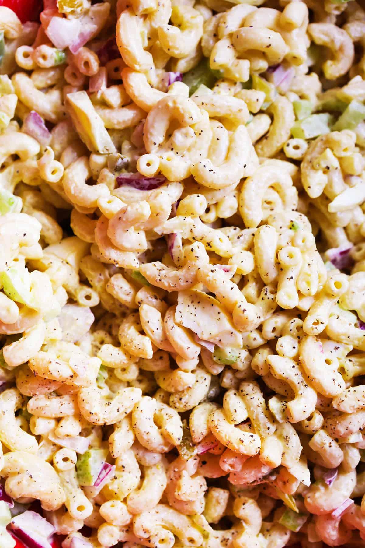 Super close up of macaroni salad in mixing bowl.