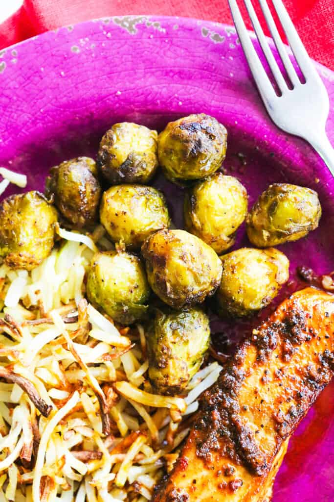 Plate of hashbrowns and brussel sprouts and salmon, ready to eat.