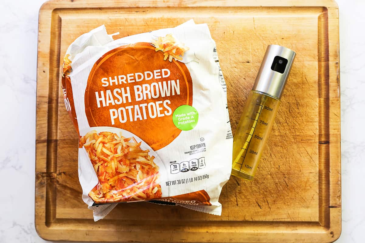 Bag of hash brown potatoes on a cutting board next to oil spritzer.