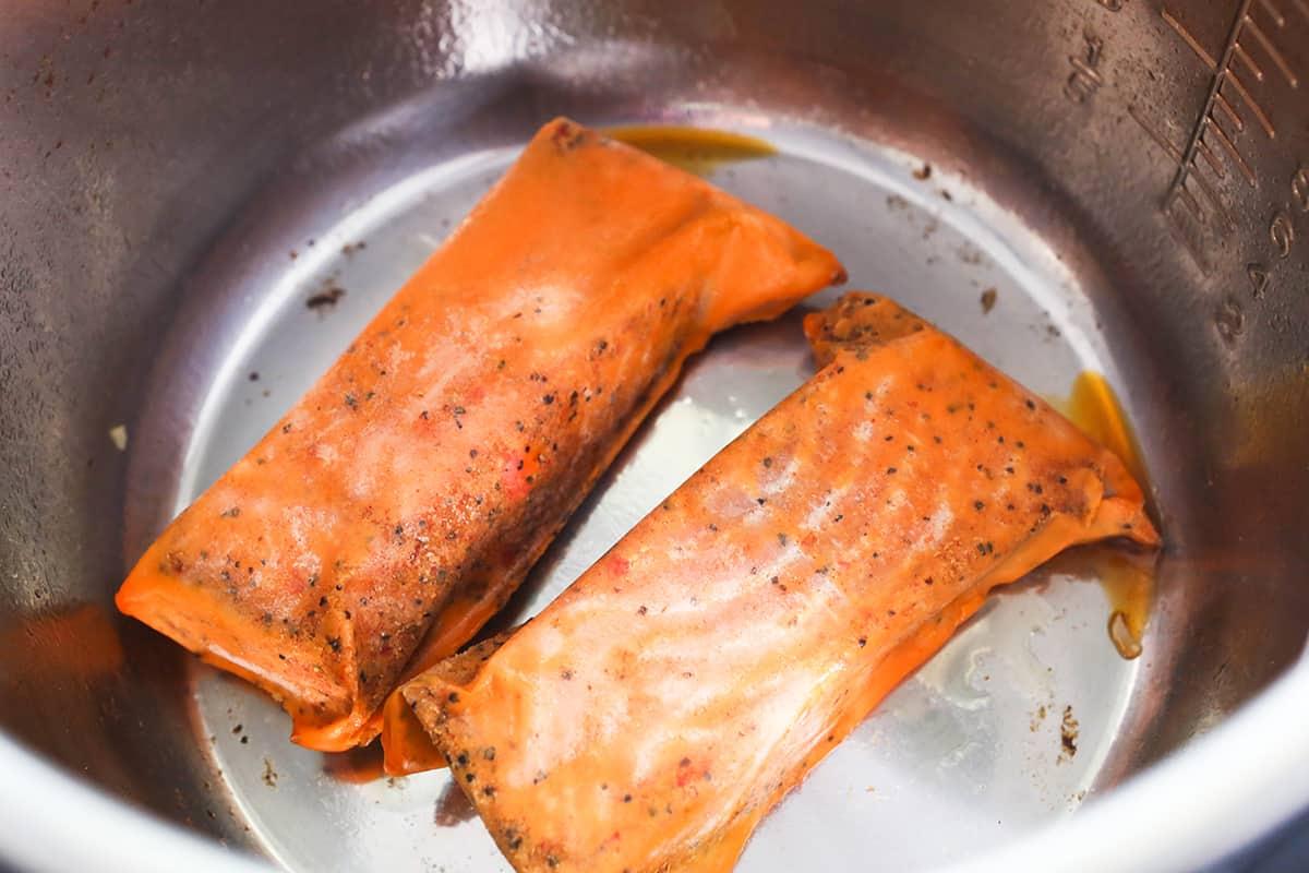 Two frozen salmon fillets inside an air fryer.