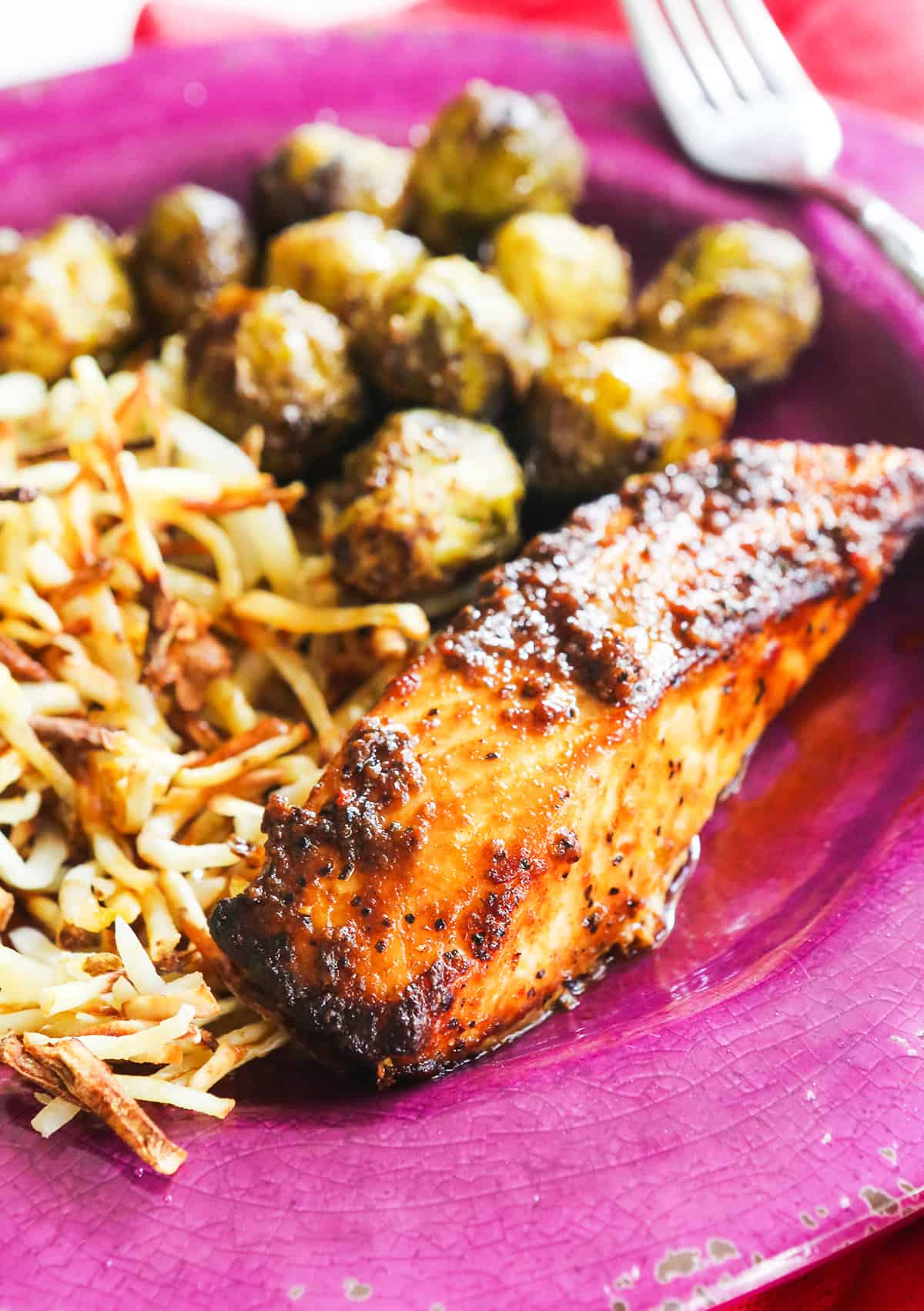 Salmon, hash browns and Brussels sprouts on a pink plate ready to eat.