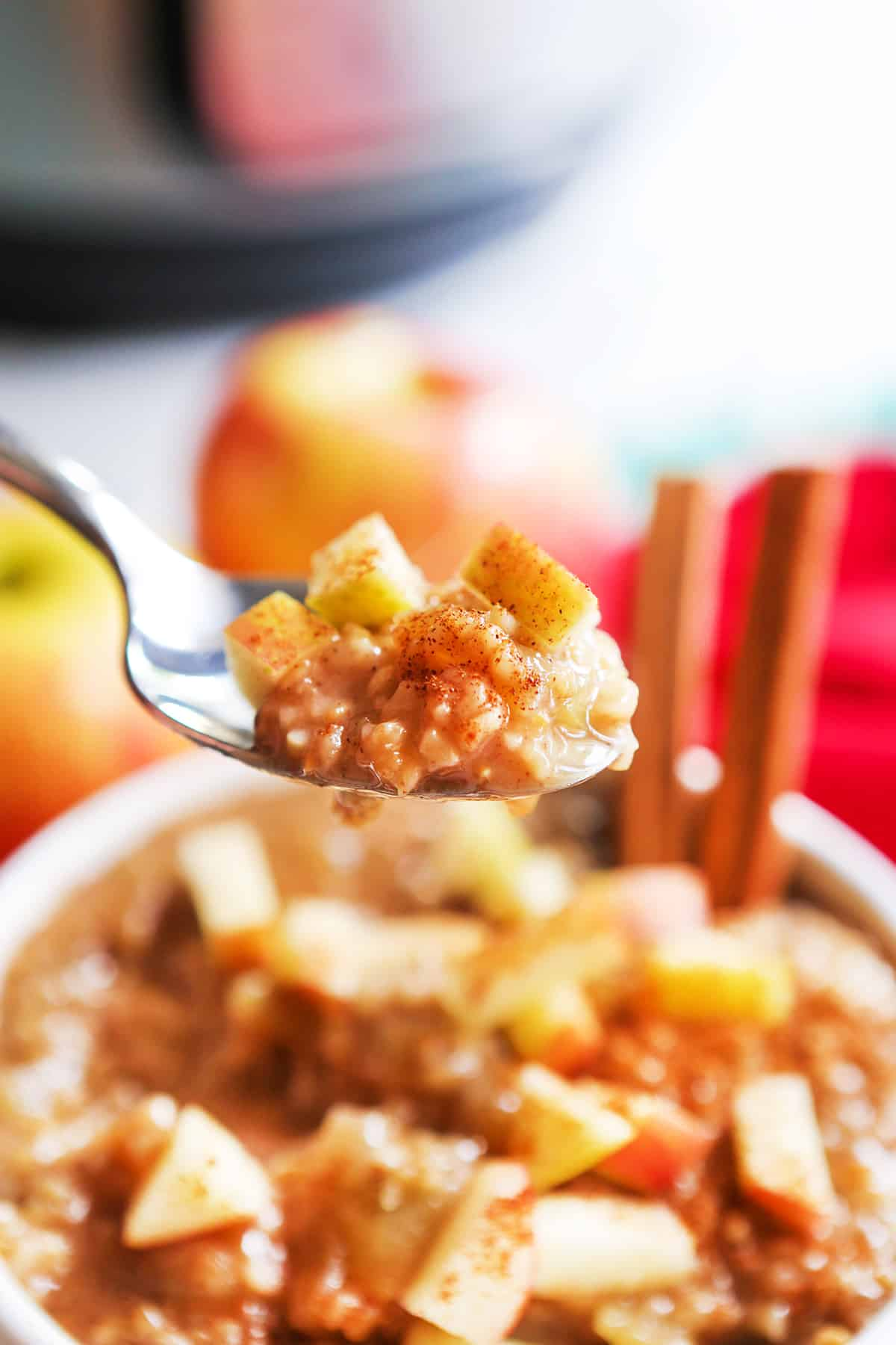 Spoon full of instant pot apple oatmeal in front of the bowl.