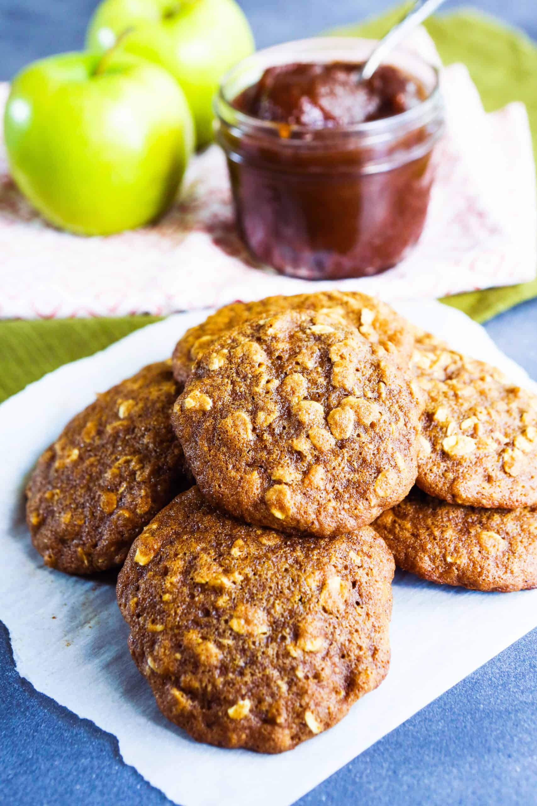 plate full of apple butter oatmeal cookies with a jar of apple butter in the background.