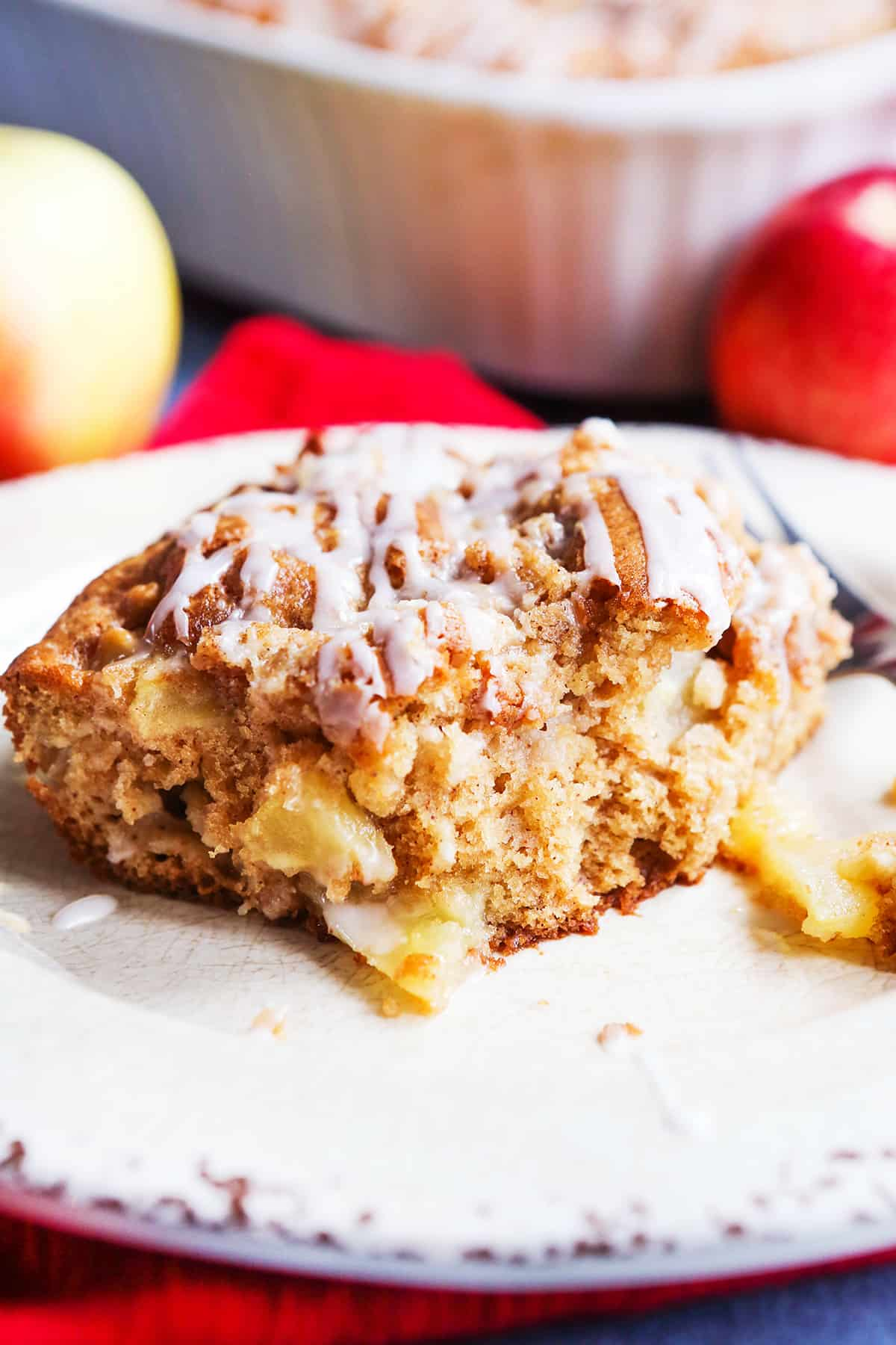 close up of piece of apple coffee cake on white plate.