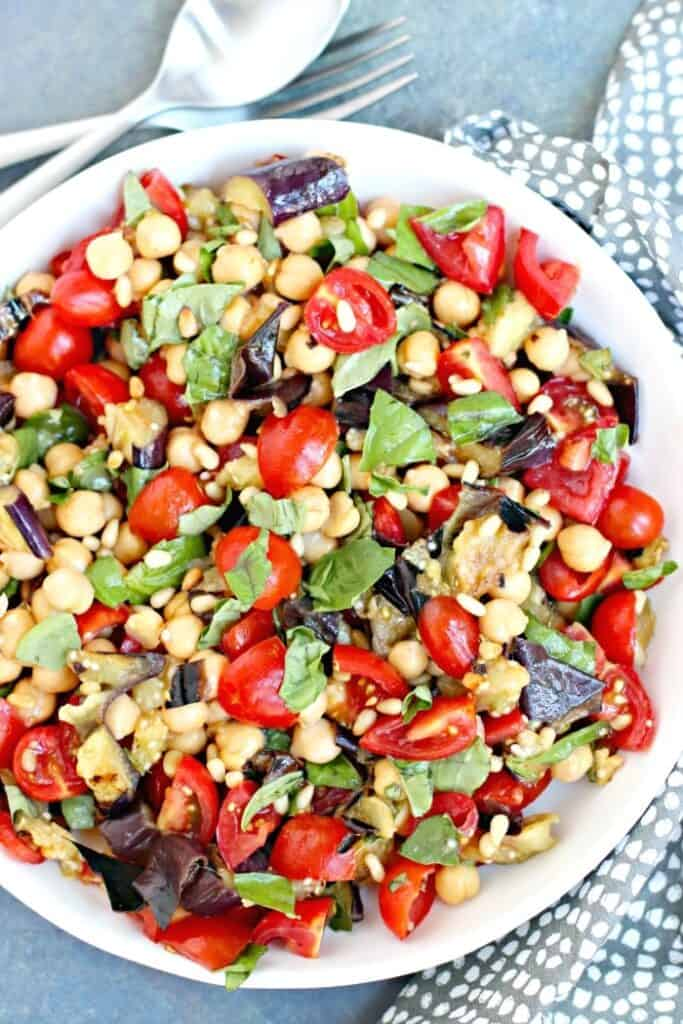 Bowl full of grilled eggplant salad with chickpeas and tomatoes ready to serve on the table.