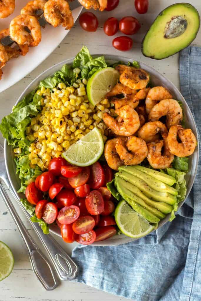 grilled shrimp, corn, avocado and tomatoes sittong on a bed of lettuce with serving utensils next to it and lime wedges on top.