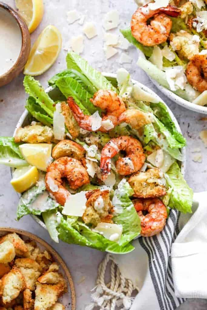 Shrimp caesar salad placed in a bowl ready to eat.