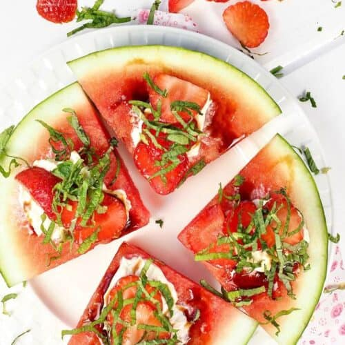 Watermelon wedge cut into 4 slices with basil and cheese sprinkled on top.