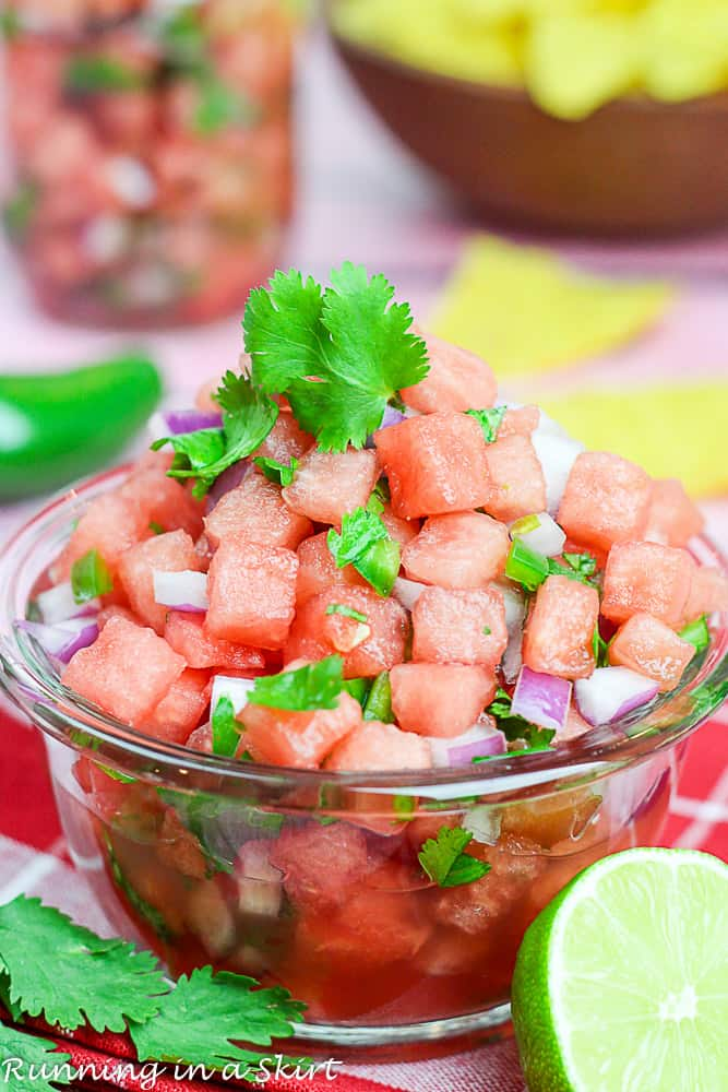 Small glass bowl of watermelon salsa with lime slices and cilantro on top.