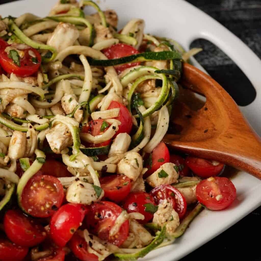 zucchini caprese salad in a serving dish and a wooden serving spoon sticking out.