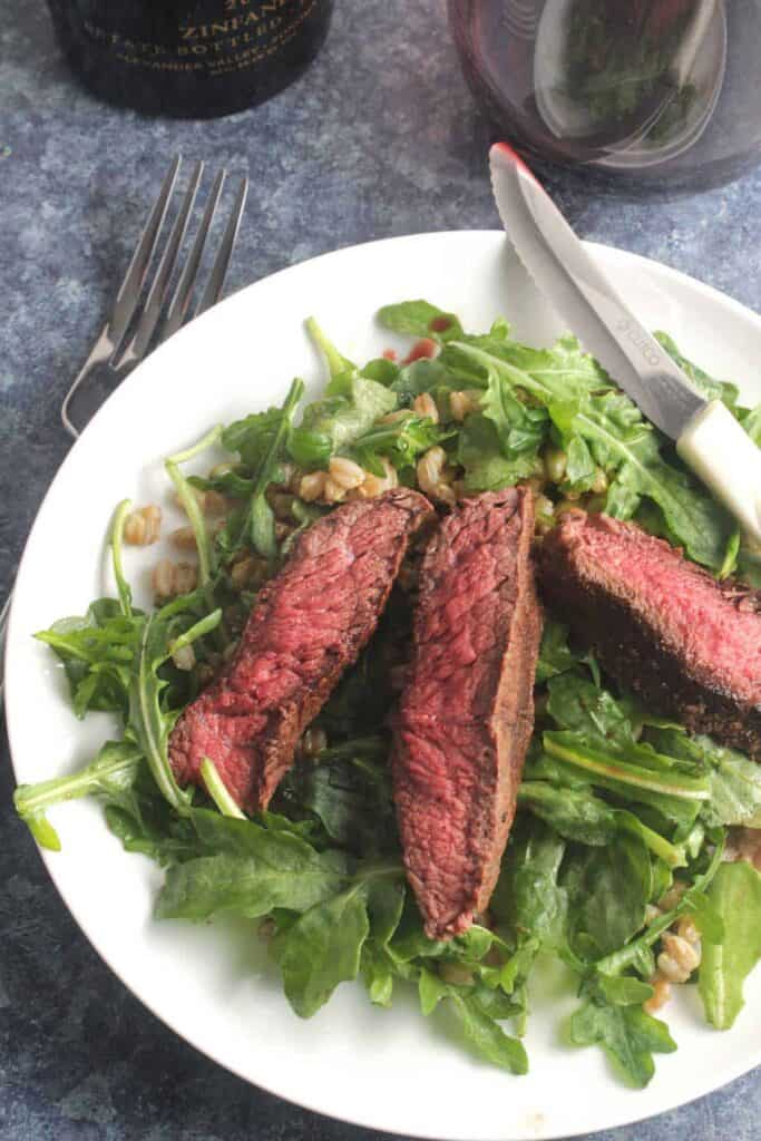 Steak sitting on a bed of arugula ready to serve on a plate.