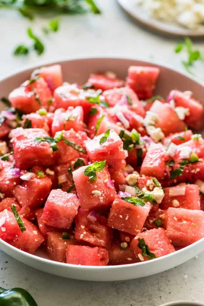cubed watermelon in a bowl sprinkled with cotija and basil on top, ready to eat.