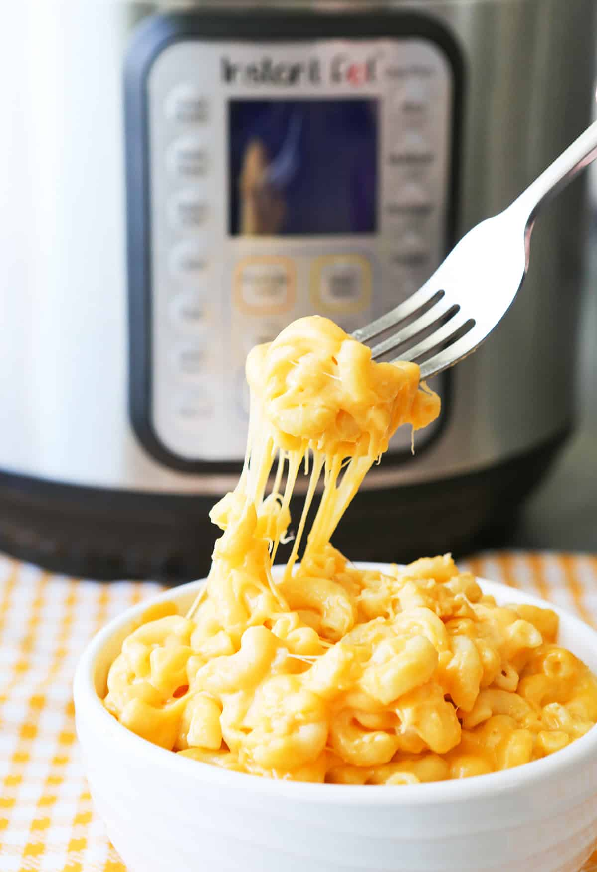 Fork pulling mac and cheese out of bowl.