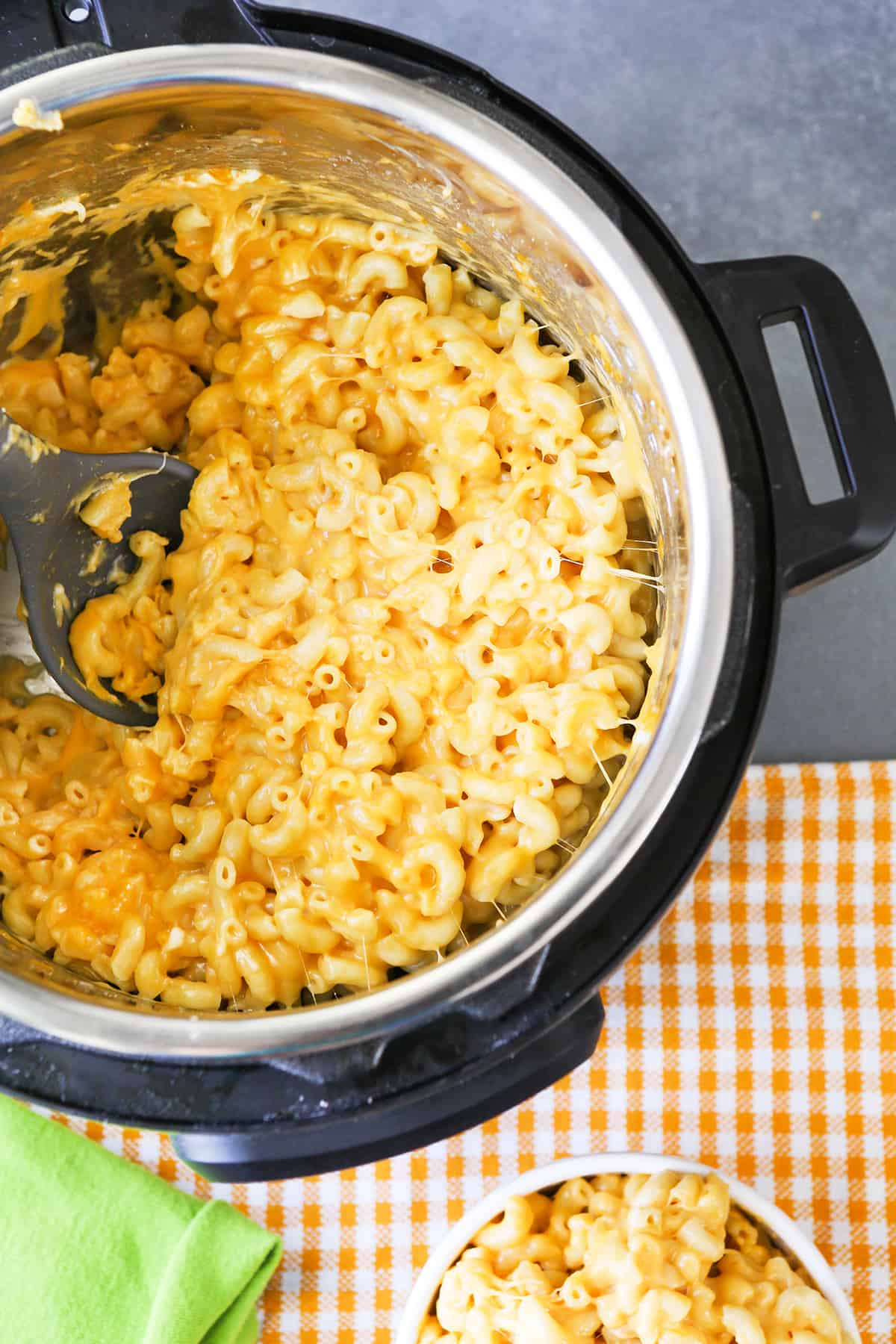 Instant Pot full of mac and cheese with bowl next to it.