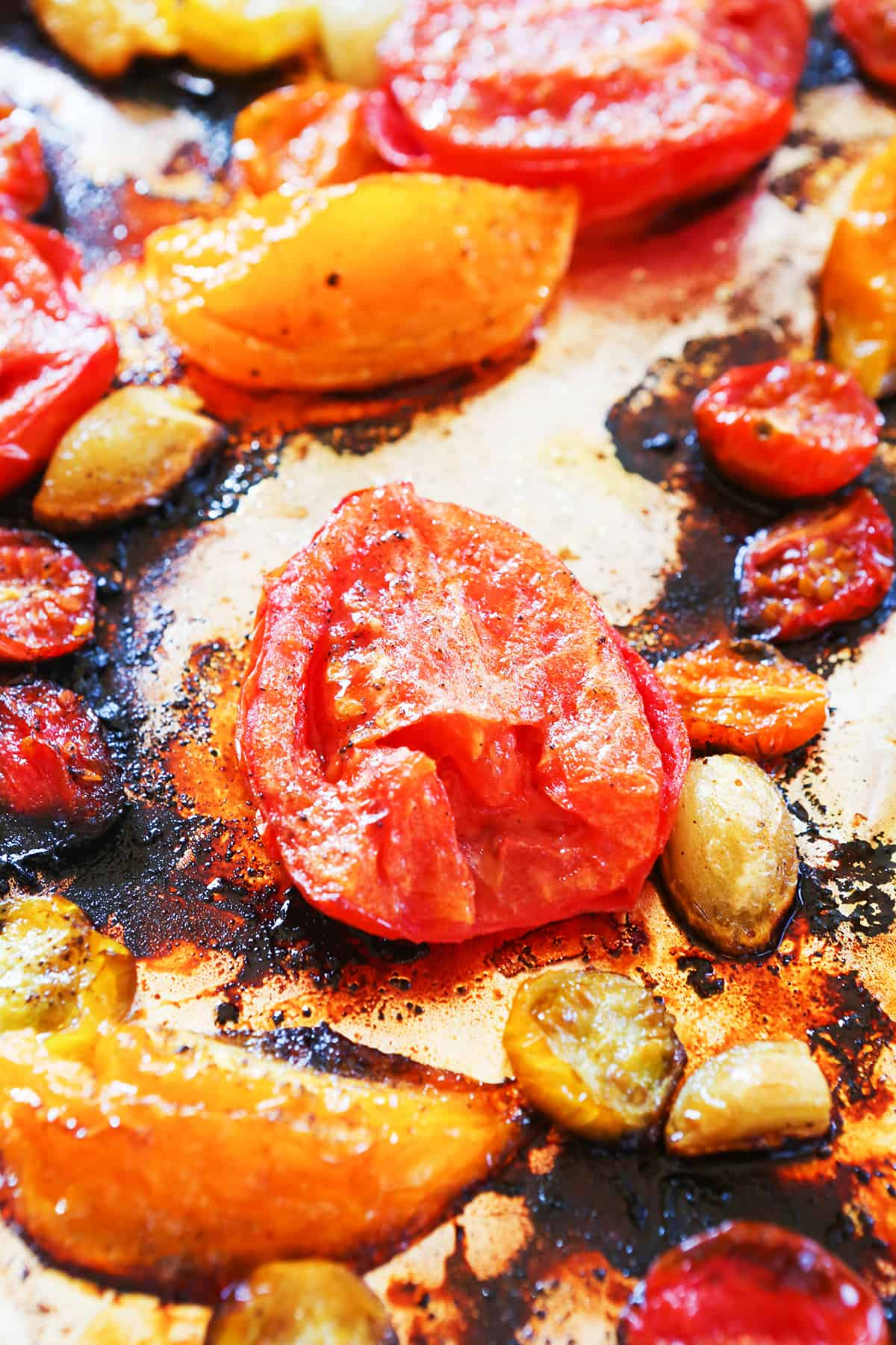 Close up of roasted Roma tomatoes on a baking sheet after cooking
