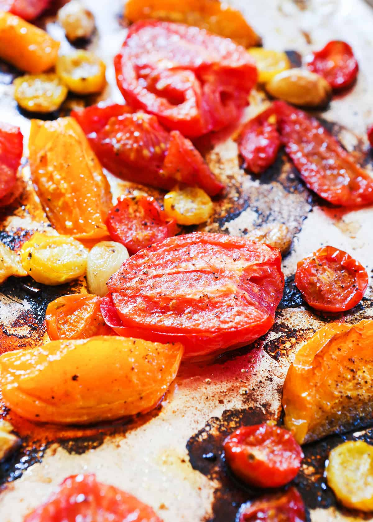 Roasted Roma and cherry tomatoes on a baking sheet.