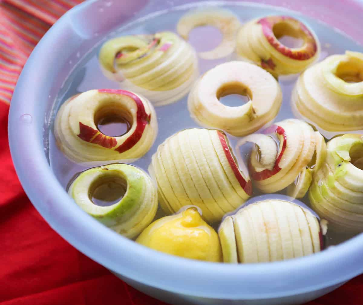 Sliced, cored apples sitting in a huge bowl filled with water.