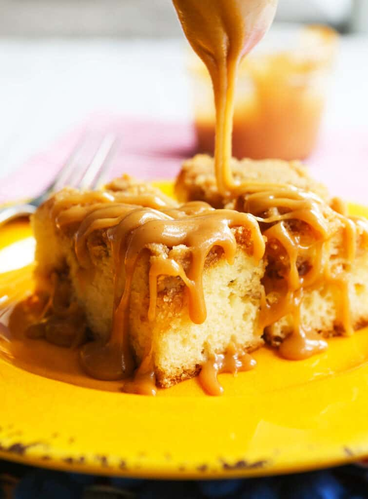 Salted caramel sauce being drizzled over piece of coffee cake.
