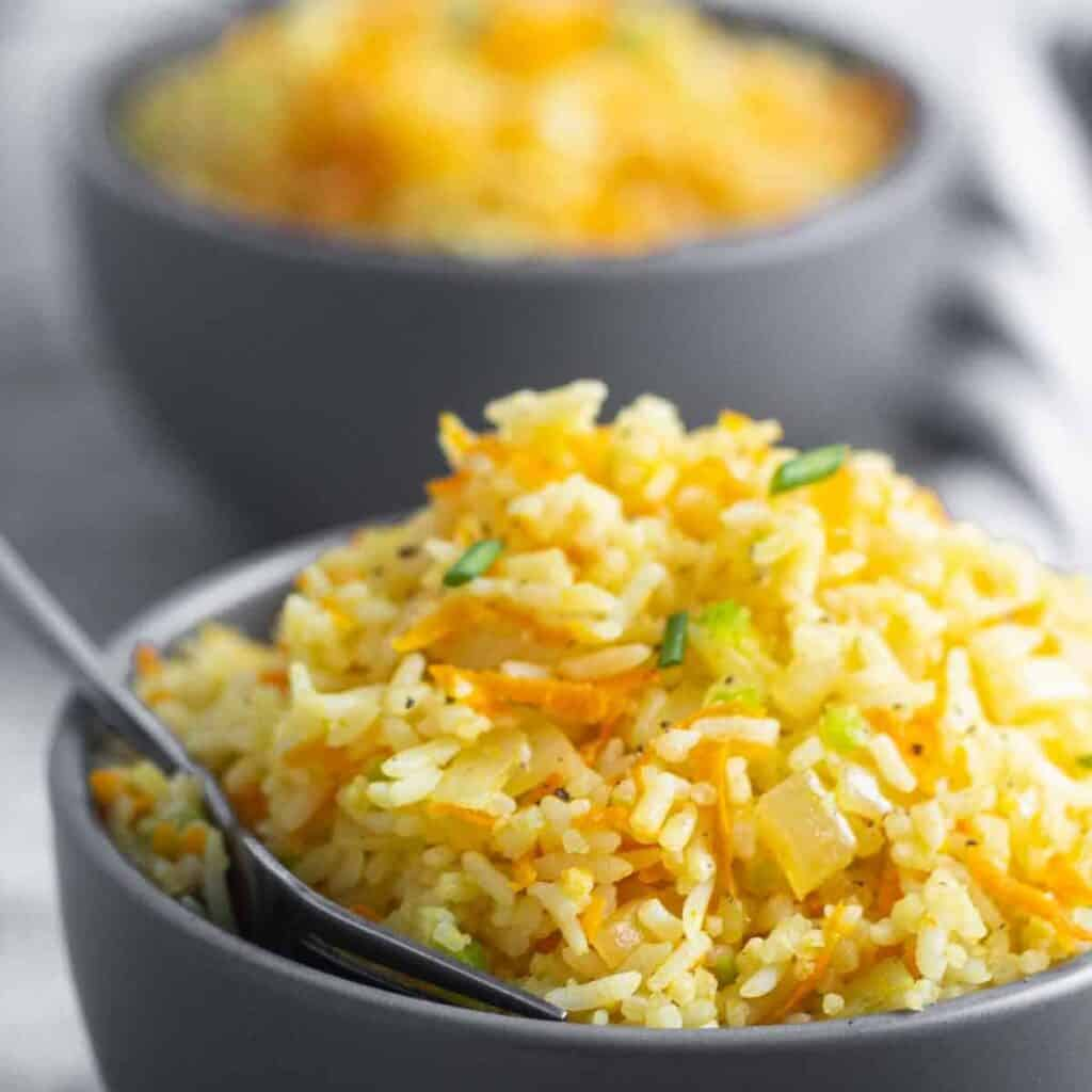 Bowl of rice and carrots with a spoon inside.