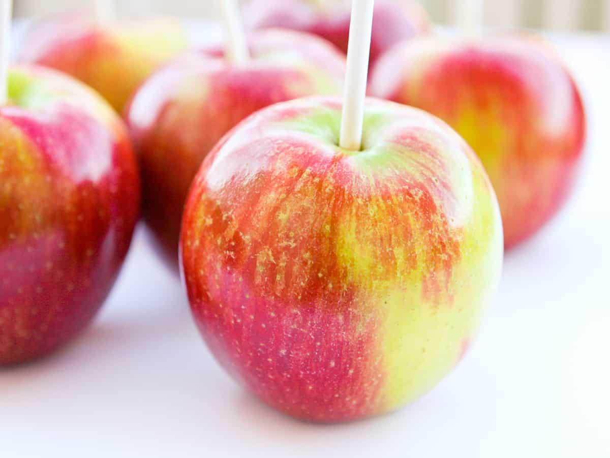 Apples with popsicle sticks jabbed into the tops.