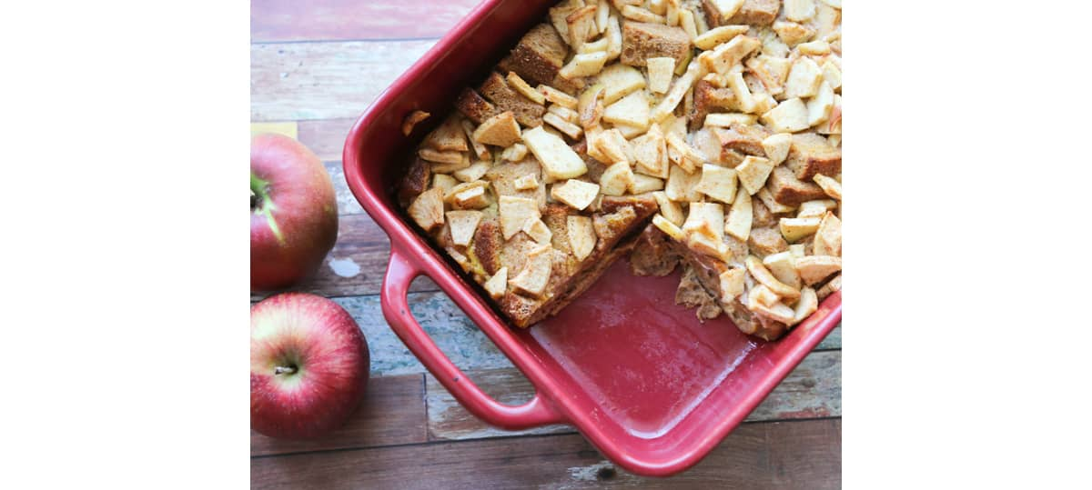 Baked apple french toast in a casserole dish with a slice missing.