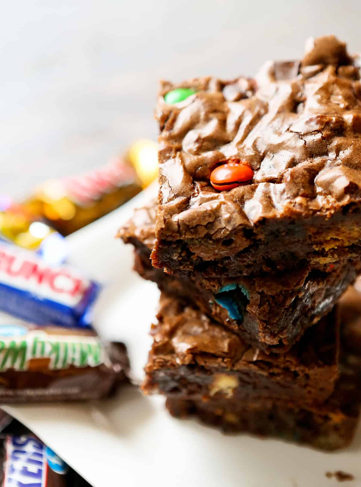 stack of candy bar brownies with fun size candy bars in background.