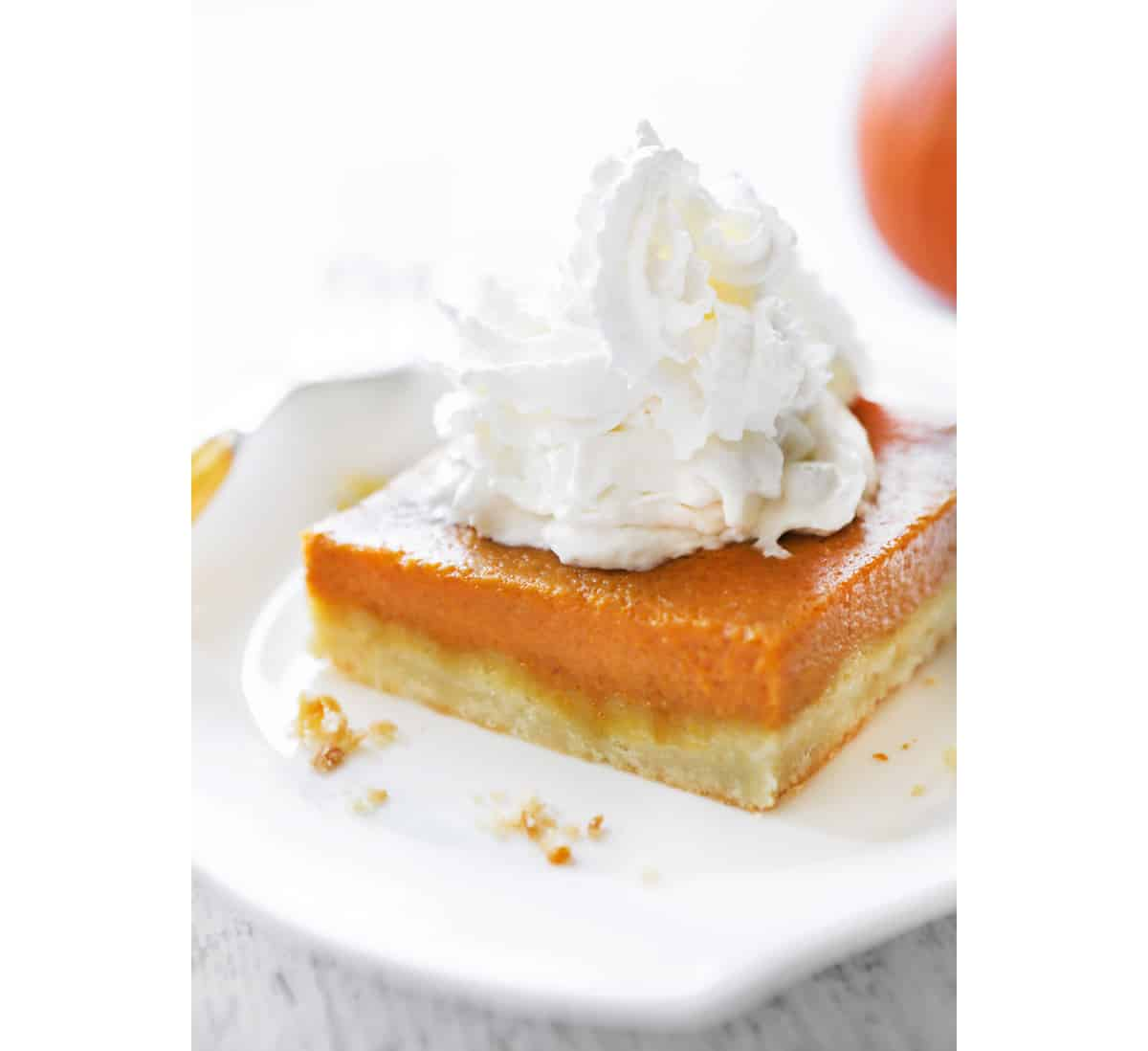 A slice of a pumpkin pie bar with whipped cream piled on top.