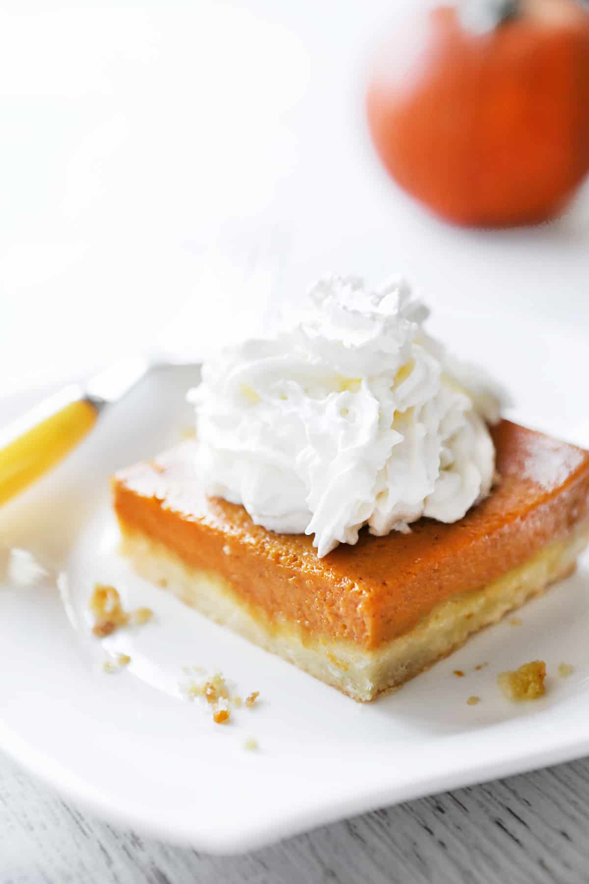 Pumpkin pie square on a plate with a fork sitting next to it.