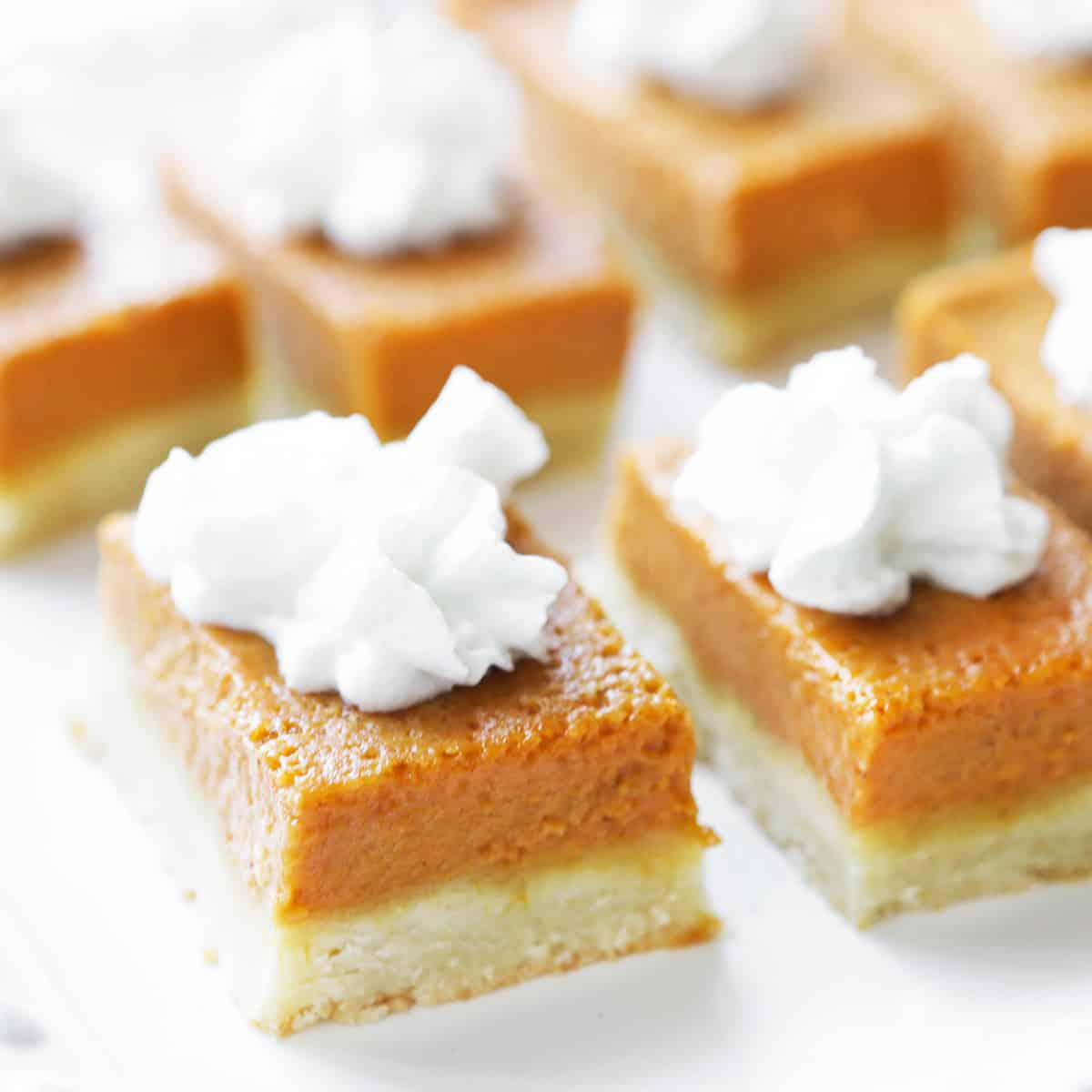 Pumpkin pie bars lined up on a serving plate, with whipped cream on top.