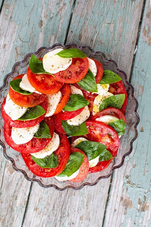 Caprese salad stacked on each other around the pie plate, sprinkled with olive oil, salt and pepper.