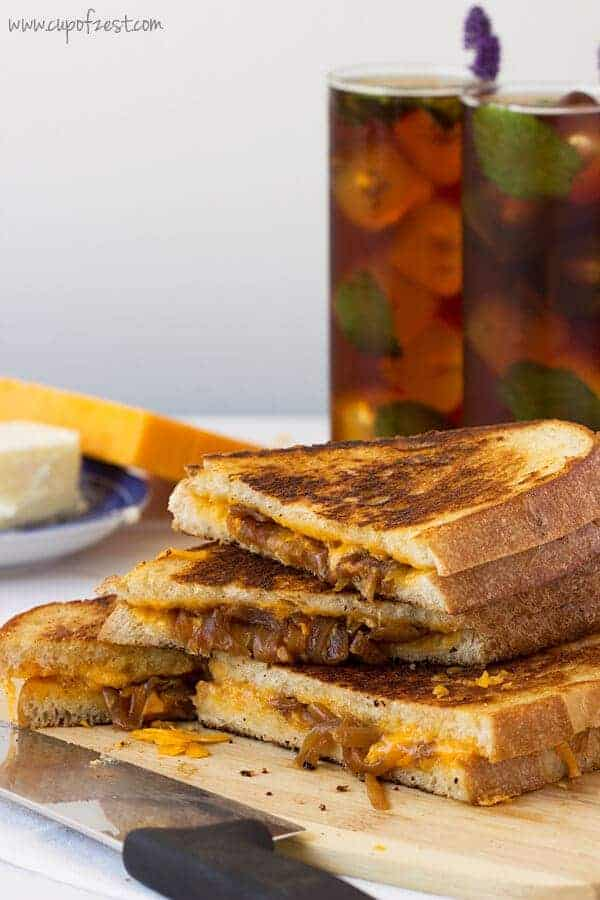Apple cider vinegar caramelized onion grilled cheese sandwiches cut diagnolly and stacked on top of one another on a plate next to a couple of glasses of ice tea.
