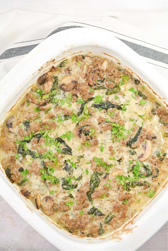 Ground beef casserole with mushrooms and spinach baked and ready to serve in a casserole dish.
