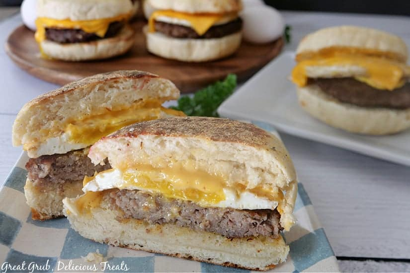A sausage, egg and cheese biscuit sliced in a half, sitting on a plate ready to be enjoyed.