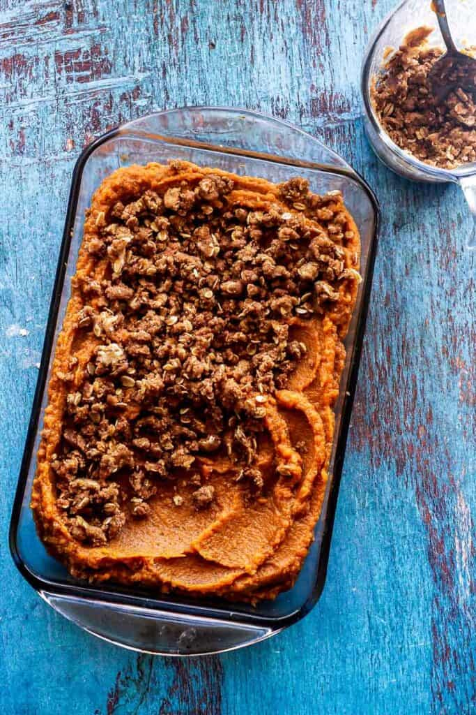 Casserole glass dish of sweet potato casserole with 2/3 covered in brown sugar topping and a section without.