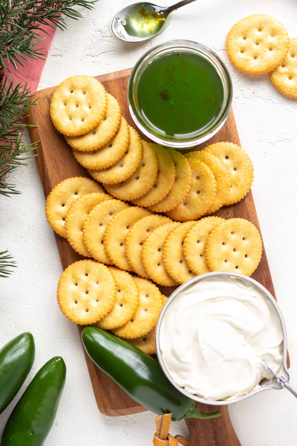 Top view of crackers lined up with cream cheese and hot pepper jelly.