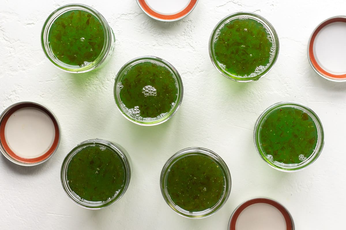 Top view of mason jars filled with green jelly.